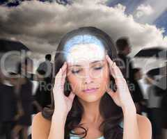 Composite image of pretty brunette with a headache