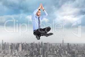 Composite image of calm businessman sitting in lotus pose with h