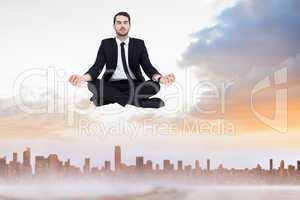Composite image of peaceful businessman sitting in lotus pose re