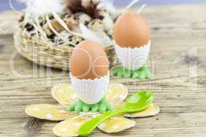 Two Boiled Eggs in Egg Cups Next to Basket of Eggs