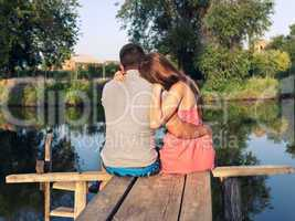 young couple sitting embracing on the bridge by the river
