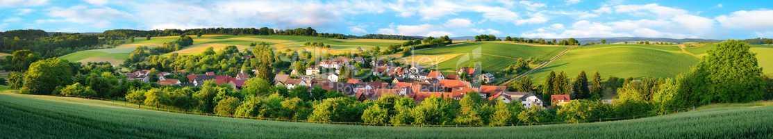Ortschaft und grüne Hügel, extra breites Panorama
