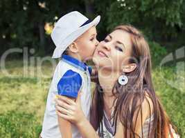 Boy kissing his mother on the cheek outdoors