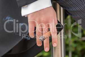 Fingers of man in tails holding cigar