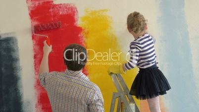 Father and daughter painting walls in bright colors