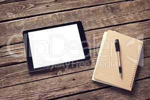 Tablet and notepad on desktop