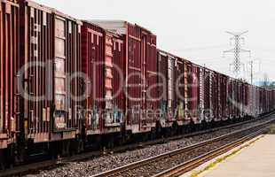 Red freight train box cars in perspective
