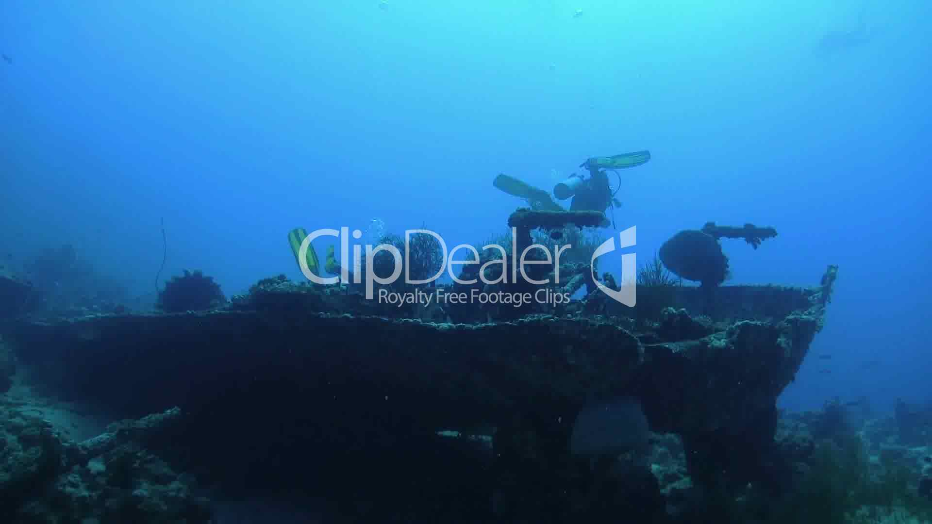 group of divers swims over ship wreck underwater scene royalty
