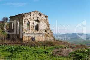 Farmhouse ruin among rural landscape