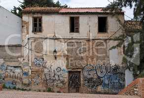 Facade of a deserted house with bricked-up windows and graffiti