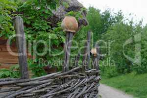 Lath fence around a farmer's house with clay pots on top of stakes in open air museum, Kiev, Ukraine