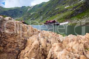Idyllic view with cottege on Balea Lake shore in Fagaras Mountai
