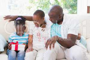 Pretty couple offer a presente for their daughter