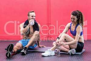 Sitting muscular couple talking together