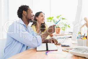 Smiling colleagues speaking together at desk