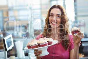 Pretty brunette showing cupcake