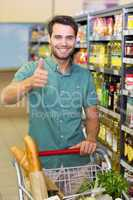 Portrait of smiling man buy products with his trollet and thumb