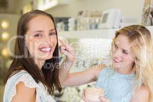 Happy blonde woman applying cosmetic products on her friend