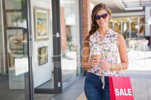 Portrait of smiling woman with sunglasses, coffee to go and shop