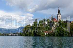 Catholic church situated on an island on Bled lake with mountains and resort on the background