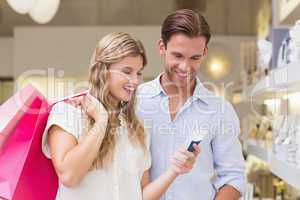 Portrait of a happy couple looking at beauty product