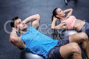 Muscular couple doing abdominal crunch