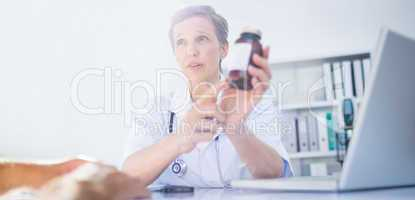 Female doctor holding a box of pills