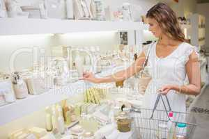 Focused woman with shopping basket browsing products