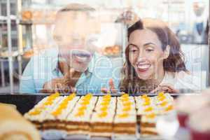 Cute couple pointing pastries through the glass