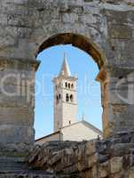 Bell tower of Saint Anthony Church in Pula, Croatia seen through the arc of Pula Amphitheater