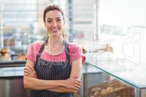 Smiling worker looking at camera with arm crossed