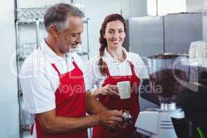 Pretty barista looking at camera and holding a mug of coffee