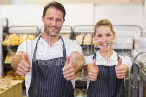 Portrait of a smiling bakers with thumb up
