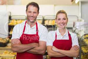 Portrait of smiling bakers with arms crossed