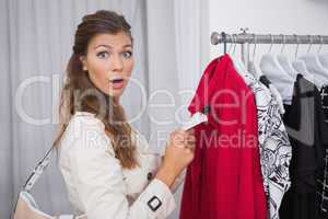 Portrait of surprised woman holding  price tag and looking at ca