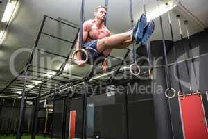 Muscular man doing ring gymnastics