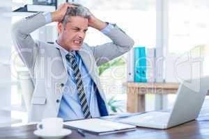 Furious businessman looking at laptop computer