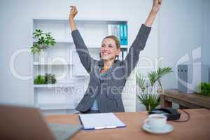 Pretty blonde businesswoman gesturing victory