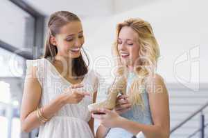 Happy women talking and holding a heel shoe