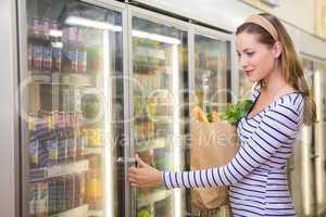 Pretty woman taking product on fridge