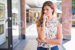 Thoughtful woman wearing blouse with floral pattern
