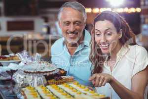 Happy couple pointing pastries