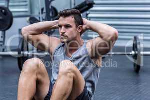 Muscular man doing abdominal crunch
