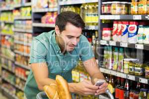 Smiling man buy food and using his smartphone