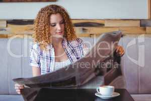 Pretty curly hair girl having cup of coffee and reading newspape