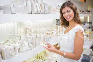Portrait of smiling woman testing moisturizer and looking at cam
