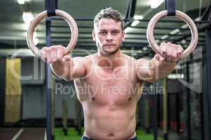 Portrait of muscular man doing ring gymnastics