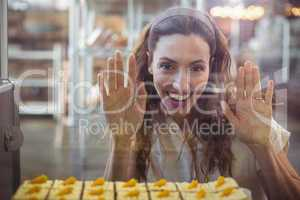Pretty brunette looking at pastries through the glass