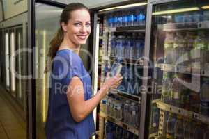 Pretty woman taking bottle of water in fridge