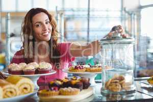 Pretty brunette smiling at camera behind plates of pastries